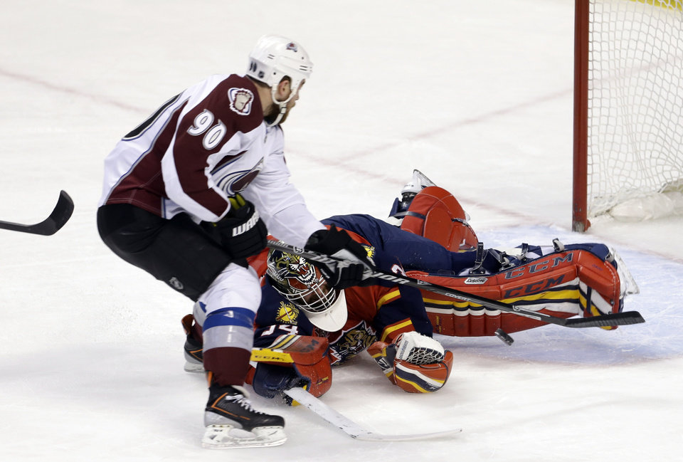 Photo - Florida Panthers goalie Tim Thomas (34) blocks a shot by Colorado Avalanche center Ryan O'Reilly (90) during the first period of an NHL hockey game in Sunrise, Fla., Friday, Jan. 24, 2014. (AP Photo/Alan Diaz)