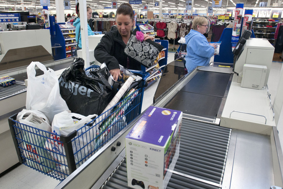 Photo -   Mandy Klocko fills her cart at a Meijer, in Grand Rapids, Mich., shortly after the store's 6AM sale began on Thanksgiving Day, Thursday, Nov. 22, 2012. Her mother, Pat Brakla, checks out behind her. Stores typically open in the wee hours of the morning on the day after Thanksgiving known as Black Friday, named for the period when stores traditionally turn a profit for the year. But Black Friday openings have crept earlier and earlier over the past few years. Now, stores from Wal-Mart to Toys R Us are opening their doors on Thanksgiving evening, hoping Americans will be willing to shop soon after they finish their pumpkin pie.(AP Photo/The Grand Rapids Press, Chris Clark ) ALL LOCAL TV OUT; LOCAL TV INTERNET OUT
