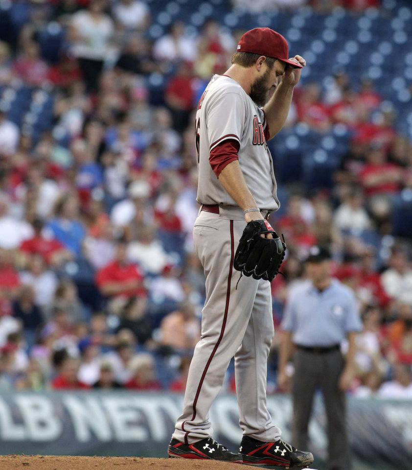 Photo - Arizona Diamondbacks starting pitcher Wade Miley walks off the mound after he walked-in the Philadelphia Phillies first run in the first inning of a baseball game on Friday, July 25, 2014, in Philadelphia. (AP Photo/H. Rumph Jr)