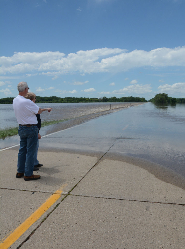 Photo - Dennis and Dottie Oleson, look at water from the Big Sioux River that covered State Highway 3, Thursday, June 19, 2014, south of of Akron, Iowa.  Cities in Iowa, Nebraska, and South Dakota are fighting a surging river after heavy rain this week pushed the waterway to record levels in some locations. (AP Photo/Dirk Lammers)