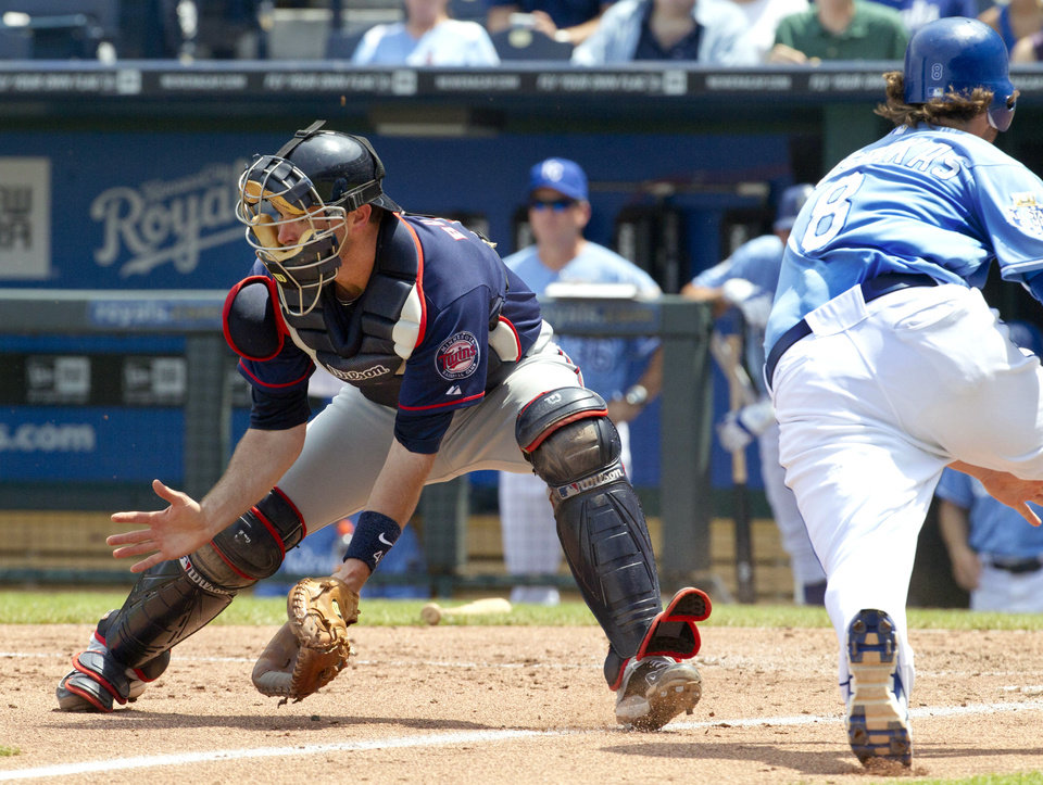 Photo -   Minnesota Twins catcher Drew Butera waits for a throw while Kansas City Royals' Mike Moustakas (8) slides home during the fourth inning of a baseball game at Kauffman Stadium in Kansas City, Mo., Sunday, July 22, 2012. Moustakas was safe on the play. (AP Photo/Orlin Wagner)
