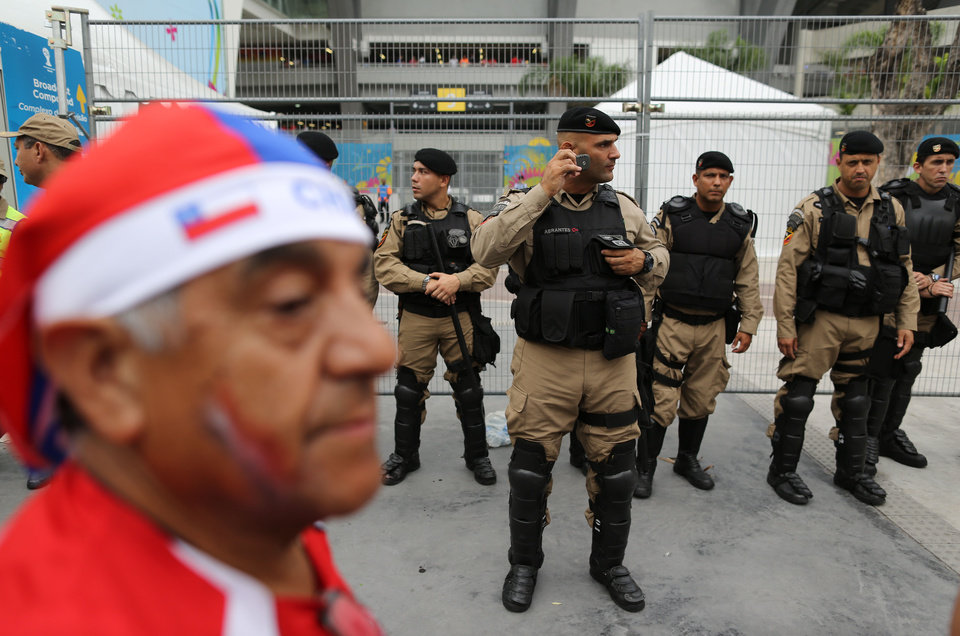 Photo - A Chile soccer fan walks by municipal guards securing the area outside the Maracana stadium where about 100 fans wearing Chilean jerseys stormed the premises before the Spain-Chile game the in Rio de Janeiro, Brazil, Wednesday June 18, 2014.  The fans entered rampaging through the media room as they desperately tried to find a way to the stands. (AP Photo/Leo Correa)