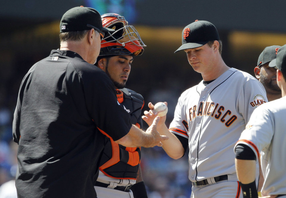 Photo - San Francisco Giants starting pitcher Matt Cain, right, is removed as he gives the baseball to manager Bruce Bochy, left, as catcher Hector Sanchez, center, watches the transaction in the sixth inning of a baseball game against the Los Angeles Dodgers, Saturday, May 10, 2014, in Los Angeles. (AP Photo/Alex Gallardo)