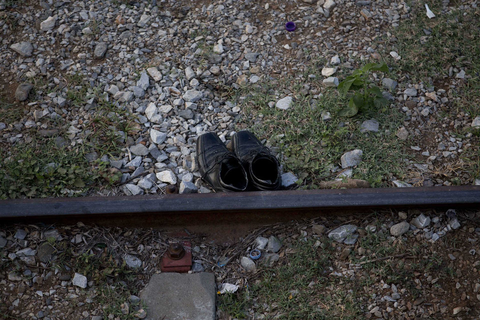 Photo - In this Saturday, July 12, 2014 photo, shoes are seen beside the train tracks in Ixtepec, Mexico. Migrants pay thousands of dollars per person for the illegal journey across thousands of miles in the care of smuggling networks that in turn pays off government officials, gangs operating on trains and drug cartels controlling the routes north. (AP Photo/Eduardo Verdugo)