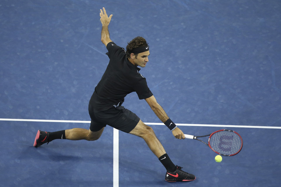 Photo - Roger Federer, of Switzerland, hits a backhand to Gael Monfils, of France, during the quarterfinals of the U.S. Open tennis tournament, Thursday, Sept. 4, 2014, in New York. (AP Photo/John Minchillo)