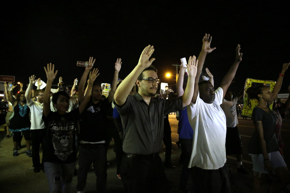 Photo - Protesters march down the street in Ferguson, Mo. Tuesday, Aug. 19, 2014. On Saturday, Aug. 9, 2014, a white police officer fatally shot Michael Brown, an unarmed black teenager, in the St. Louis suburb. (AP Photo/Jeff Roberson)