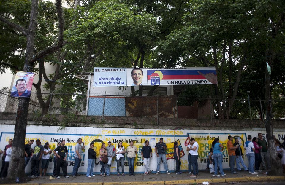 Photo -   Residents line up at a polling station to vote in presidential elections in Caracas, Venezuela, Sunday, Oct. 7, 2012. President Hugo Chavez is running against opposition candidate Henrique Capriles.(AP Photo/Sharon Steinmann)