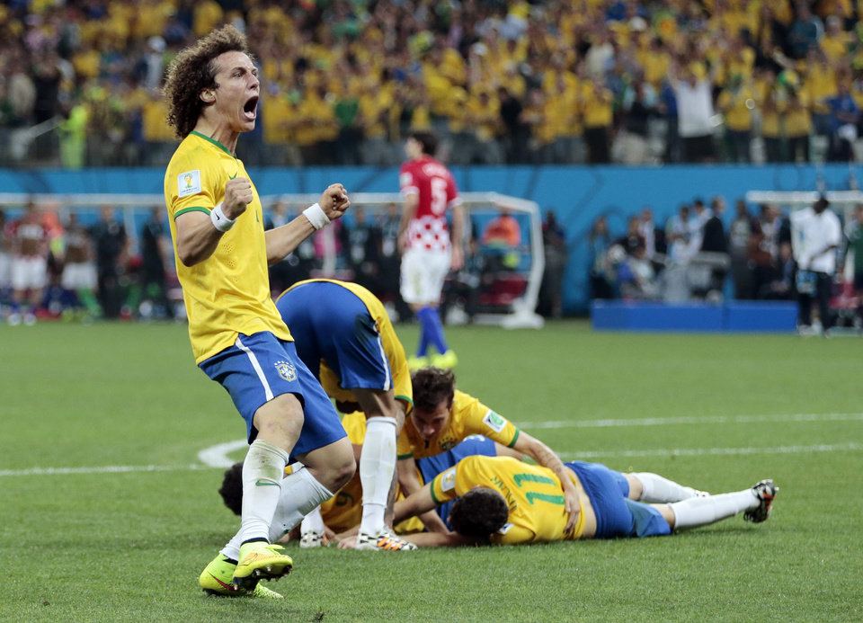Photo - Brazil's David Luiz (4) celebrates teammate Oscar's (11) goal during the group A World Cup soccer match between Brazil and Croatia, the opening game of the tournament, in the Itaquerao Stadium in Sao Paulo, Brazil, Thursday, June 12, 2014.  (AP Photo/Ivan Sekretarev)