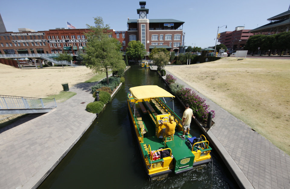 Oklahoma City is applying for a federal grant to convert the Bricktown water taxi fleet to electric power. The taxis, like the one shown here Wednesday, are powered by gasoline. <strong>Steve Gooch</strong>