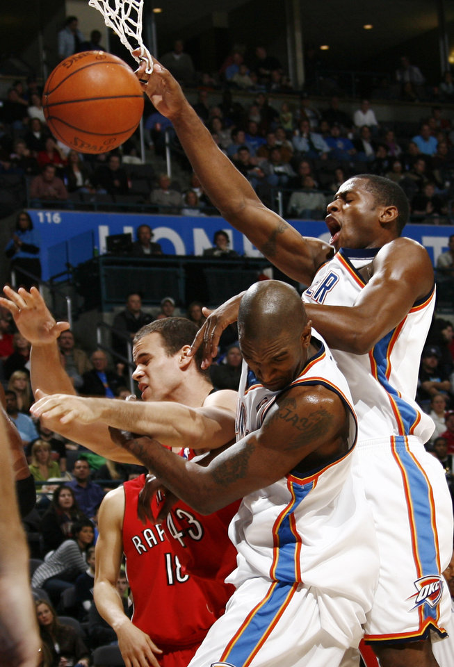 Photo - Oklahoma City's Desmond Mason, right, Joe Smith, middle, and Toronto's Kris Humphries collide on a rebound attempt during the NBA basketball game between the Toronto Raptors and the Oklahoma City Thunder at the Ford Center in Oklahoma City, Friday, Dec. 19, 2008. BY NATE BILLINGS, THE OKLAHOMAN