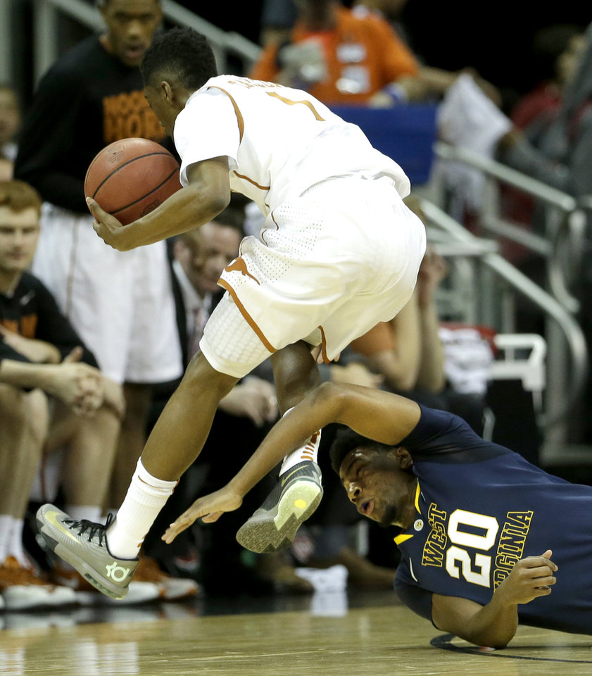 Photo - Texas' Isaiah Taylor (1) and West Virginia's Brandon Watkins (20) chase a loose ball during the first half of an NCAA college basketball game in the Big 12 men's tournament on Thursday, March 13, 2014, in Kansas City, Mo. (AP Photo/Charlie Riedel)