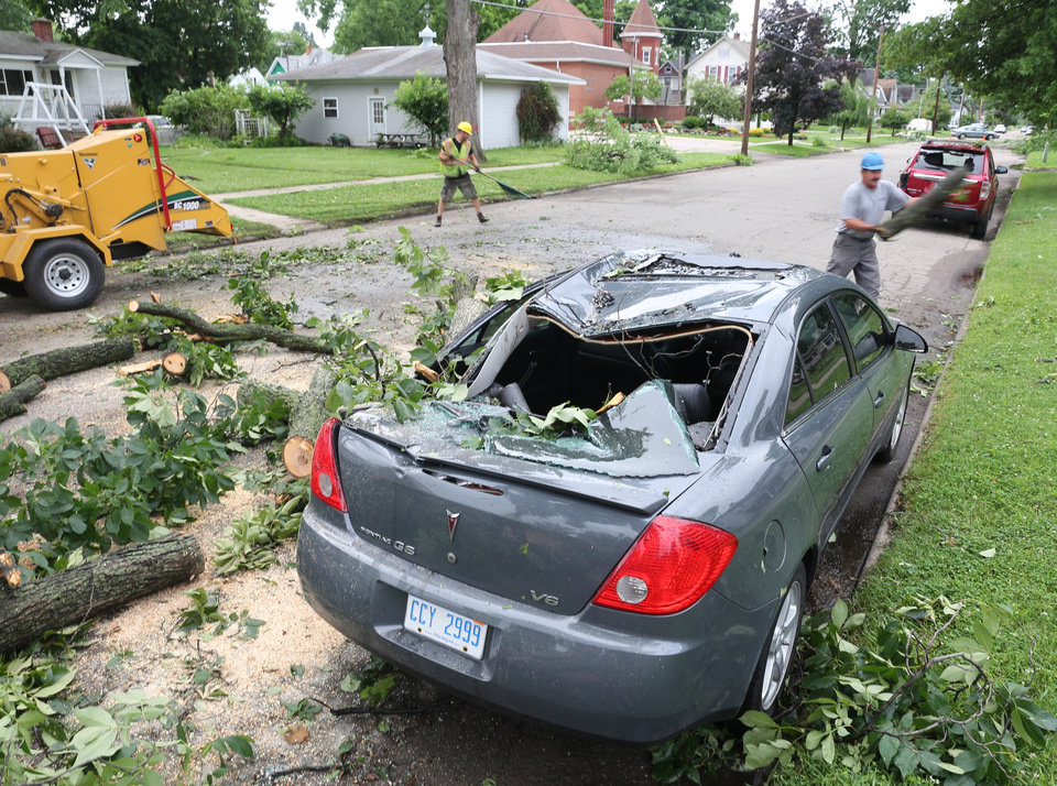 Photo - Clean up crews remove a fallen tree from a car after a storm in Vicksburg, Mich., Tuesday, July 1, 2014. Severe thunderstorms packing high winds knocked down trees and power lines across parts of Michigan, leaving more than 230,000 without power and injuring a firefighter. (AP Photo/Kalamazoo Gazette-MLive Media Group, Mark Bugnaski) ALL LOCAL TELEVISION OUT; LOCAL TELEVISION INTERNET OUT