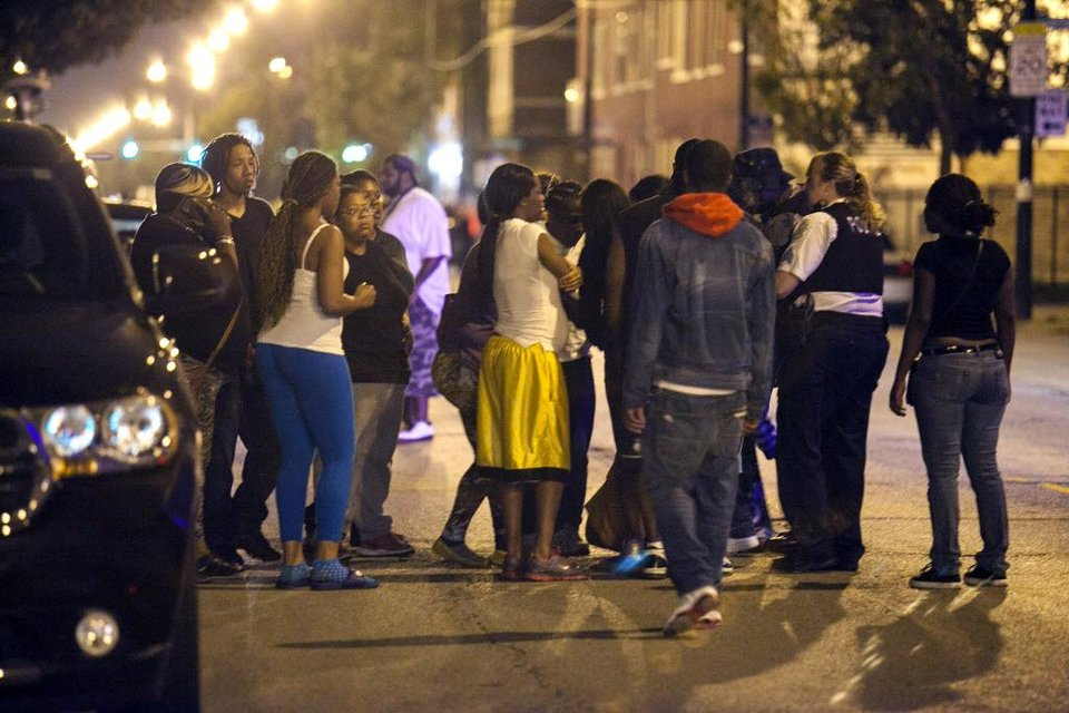 Photo - In this Thursday, Sept. 19, 2013, photo, bystanders convene near the scene of a shooting at Cornell Square Park in Chicago's Back of the Yard neighborhood that left multiple victims including a 3-year-old boy. Thursday night's attack was the latest violence in a city that has struggled to stop such shootings by increasing police patrols. (AP Photo/Sun-Times Media, Chandler West)