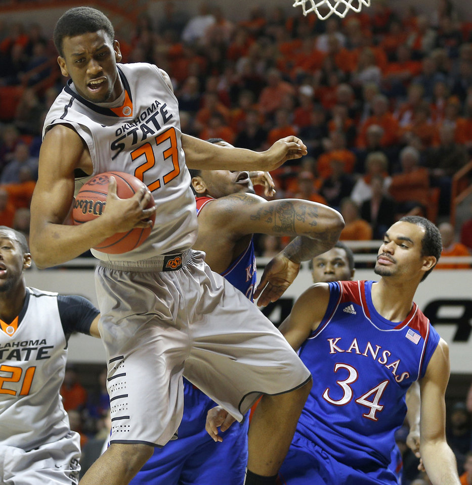 Photo - Oklahoma State's Leyton Hammonds (23) grabs a rebound beside Kansas' Perry Ellis (34) during an NCAA college basketball game between Oklahoma State University (OSU) and the University of Kansas at Gallagher-Iba Arena in Stillwater, Okla., Saturday, March 1, 2014. Photo by Bryan Terry, The Oklahoman