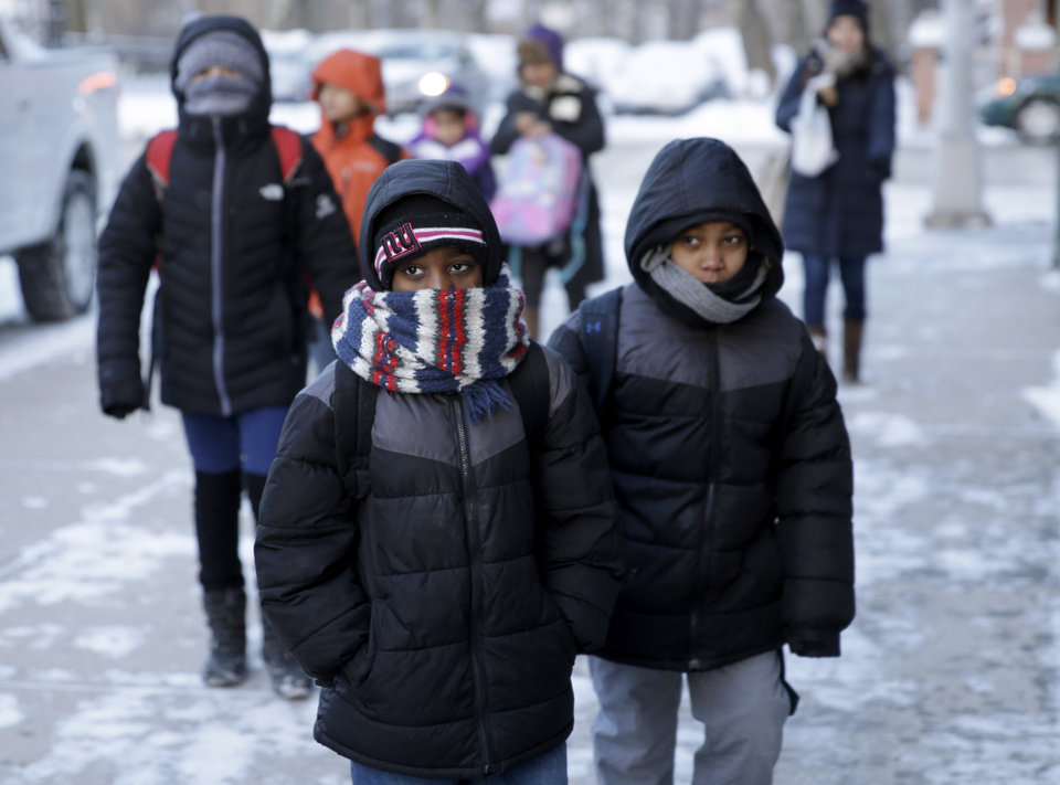 Photo - Children arrive to school bundled up against the cold in the Brooklyn borough of New York, Wednesday, Jan. 22, 2014.  A winter storm stretched from Kentucky to New England and hit hardest along the heavily populated Interstate 95 corridor between Philadelphia and Boston. Snow began falling at midmorning Tuesday in Philadelphia and dumped as much as 14 inches by Wednesday morning, with New York seeing almost as much.  Boston and Philadelphia officials ordered schools closed Wednesday, but in New York City, the nation's largest public school system remained open. (AP Photo/Seth Wenig)