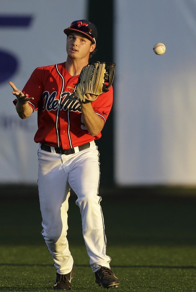 Photo - Mississippi outfielder Auston Bousfield (9) loses the ball in the sun as it hits his glove, allowing a run to score, in the third inning of an NCAA college baseball tournament super regional game against Louisiana Lafayette in Lafayette, La.,Saturday, June 7, 2014. (AP Photo/Gerald Herbert)