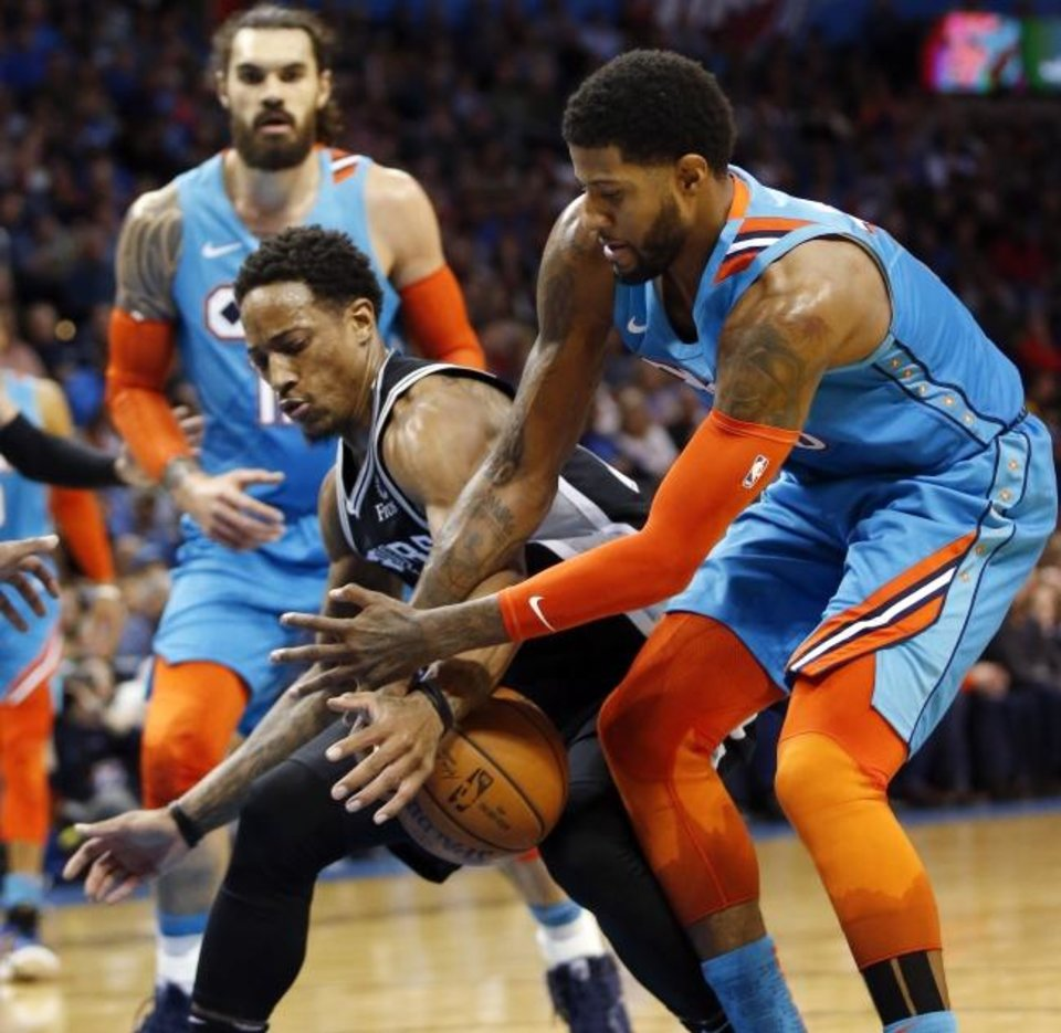 Photo -  The Thunder's Paul George (13) and the Spurs' DeMar DeRozan (10) battle for a loose ball in January. The Thunder and the Spurs have been model NBA franchises despite small markets. [Nate Billings/The Oklahoman]