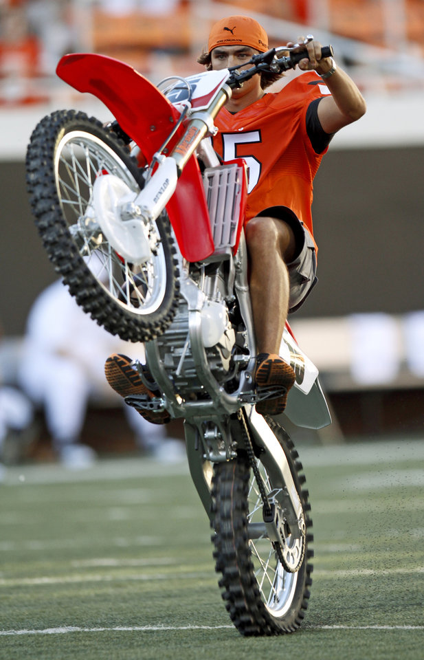 Photo - Former OSU golfer Rickie Fowler rides a motorcycle during the game between Oklahoma State and Arizona on Thursday. PHOTO BY BRYAN TERRY, The Oklahoman