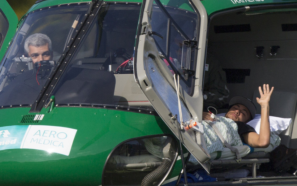 Photo - Brazil's Neymar waves from inside a medical helicopter at the Granja Comary training center, in Teresopolis, Brazil, Saturday, July 5, 2014. Neymar was airlifted from Brazil's training camp Saturday and will be treated at home for his back injury. Neymar, the biggest football star in Brazil, was ruled out of the rest of the World Cup after fracturing his third vertebra during Friday's 2-1 quarterfinal win over Colombia. (AP Photo/Leo Correa)