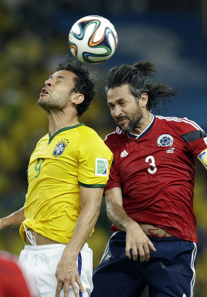 Photo - Brazil's Fred and Colombia's Mario Yepes go for a header during the World Cup quarterfinal soccer match between Brazil and Colombia at the Arena Castelao in Fortaleza, Brazil, Friday, July 4, 2014. (AP Photo/Hassan Ammar)
