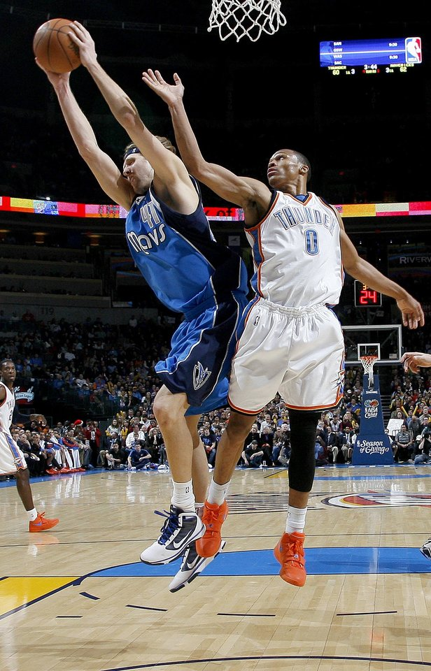 Photo - Dirk Nowitzki of Dallas grabs a rebound beside Russell Westbrook of Oklahoma City during the NBA basketball game between the Oklahoma City Thunder and the Dallas Mavericks at the Ford Center in Oklahoma City on Wednesday, December 16, 2009. Photo by Bryan Terry, The Oklahoman