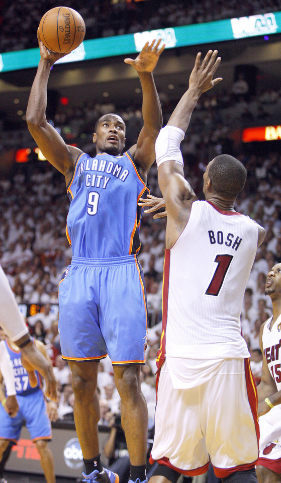 Photo - The Thunder's Serge Ibaka, left, shoots over Miami's Chris Bosh during Game 4 of the NBA Finals on Tuesday night. Photo by Bryan Terry,  The Oklahoman