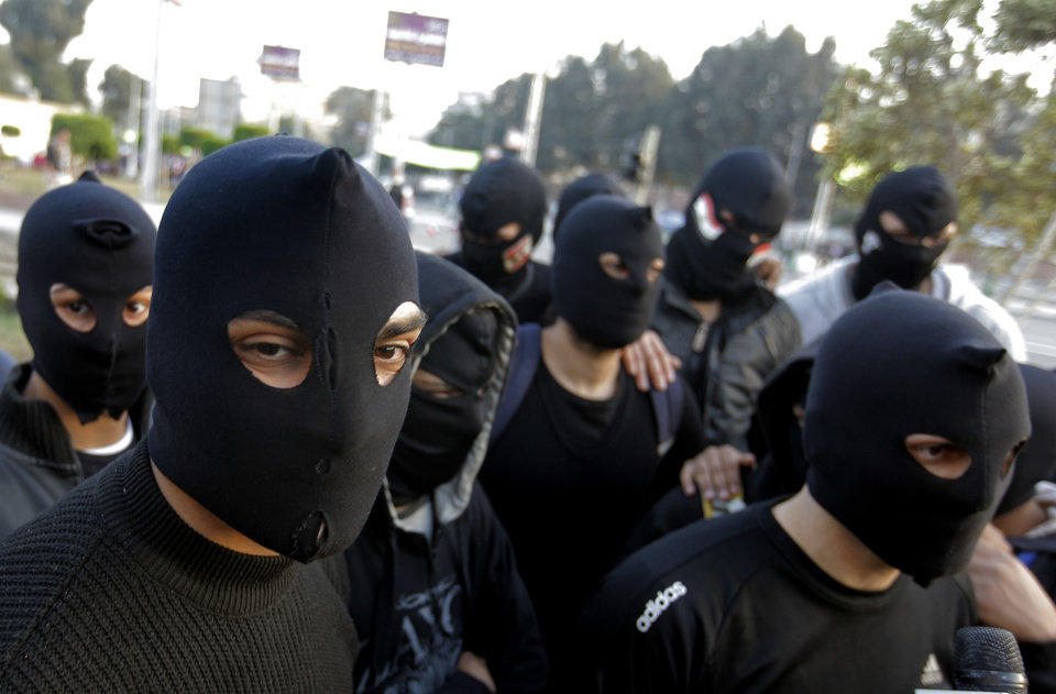 Egyptian masked protesters, who call themselves the black eagles and describes themselves as peaceful but are prepared to defend any attacks against protesters, gather near the presidential palace in Cairo, Egypt, Friday, Jan. 25, 2013. Two years after Egypt's revolution began, the country's schism was on display Friday as the mainly liberal and secular opposition held rallies saying the goals of the pro-democracy uprising have not been met and denouncing Islamist President Mohammed Morsi. (AP Photo/Amr Nabil) ORG XMIT: AMR119