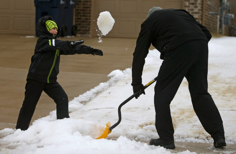 Photo - Patrick Free, 6, throws a pile of sleet at his father, Pat Free, as he shovels their sidewalk in northwest Oklahoma City, Sunday, December 27, 2015. Photo by Bryan Terry, The Oklahoman