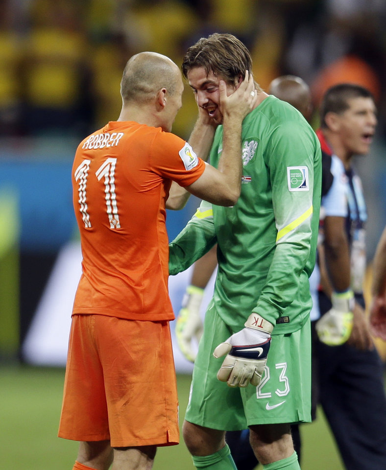 Photo - Netherlands' Arjen Robben congratulates goalkeeper Tim Krul after the Netherlands defeated Costa Rica 4-3 in a penalty shootout after a 0-0 tie during the World Cup quarterfinal soccer match at the Arena Fonte Nova in Salvador, Brazil, Saturday, July 5, 2014. (AP Photo/Natacha Pisarenko)
