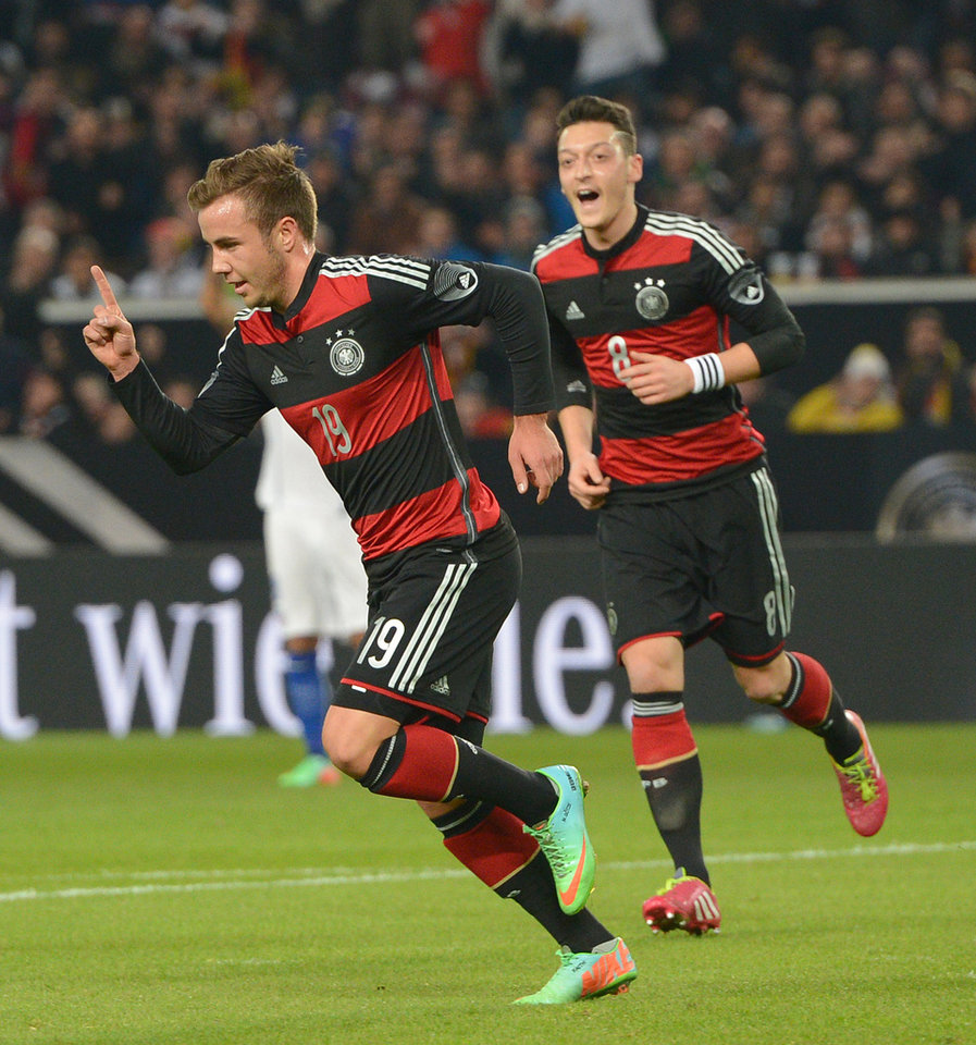 Photo - Germany's  Mario Goetze , left, celebrates after he scored the opening goal while teammate Mesut Ozil, right looks on, during the friendly soccer match between Germany and Chile in Stuttgart, Germany, Wednesday March 5, 2014. (AP Photo/dpa,Bernd Weissbrod)