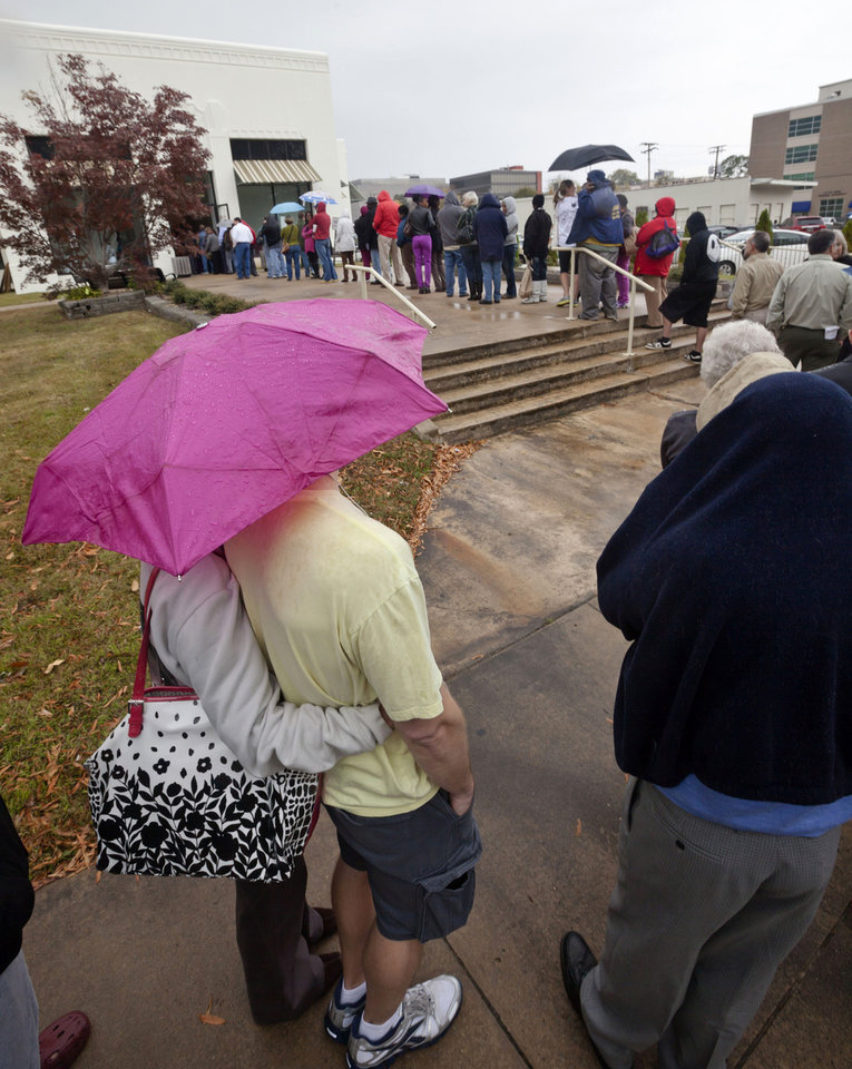 Arkansas voters line up in the rain at an early voting poling place in Little Rock, Ark., Monday, Nov. 5, 2012, the last day to vote in advance of the Nov. 6, general election. About a quarter of Arkansas' registered voters have already cast ballots in this year's general election. (AP Photo/Danny Johnston)