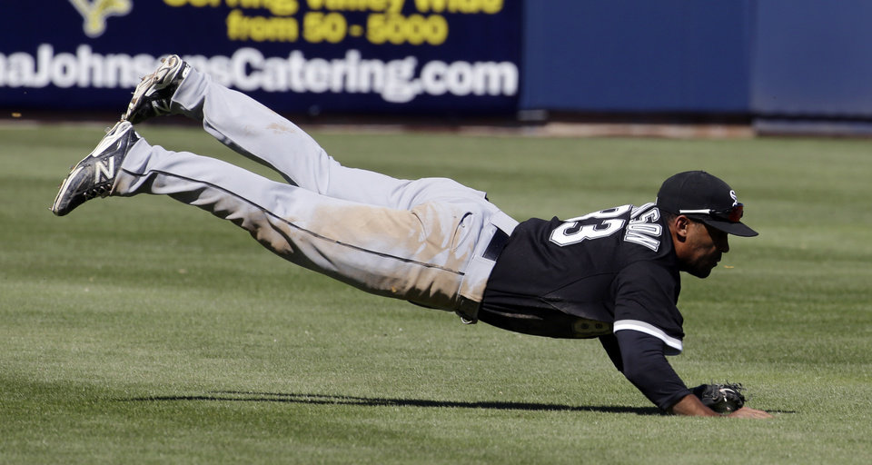 Photo - Chicago White Sox's Micah Johnson dives to catch a ball hit by Milwaukee Brewers' Mark Reynolds during the fourth inning of an exhibition spring training baseball game Monday, March 10, 2014, in Phoenix. (AP Photo/Morry Gash)