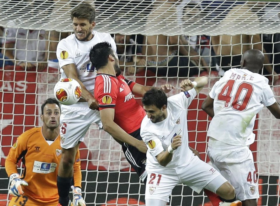 Photo - Sevilla's Daniel Carrico, left, jumps for the ball with Benfica's Ezequiel Garay, next to Sevilla's Nicolas Pareja and Stephane Mbia, right,  during the Europa League soccer final between Sevilla and Benfica, at the Turin Juventus stadium in Turin, Italy, Wednesday, May 14, 2014. (AP Photo/Andrew Medichini)