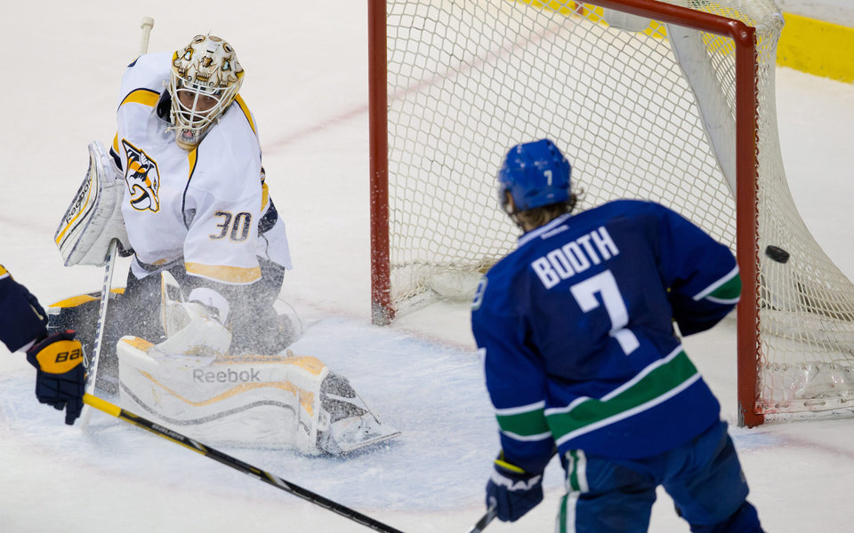 Photo - Nashville Predators goalie Carter Hutton, left, and Vancouver Canucks' David Booth watch as a Canucks shot goes wide of the goal during the second period of an NHL hockey game Wednesday, March 19, 2014. (AP Photo/The Canadian Press, Darryl Dyck)