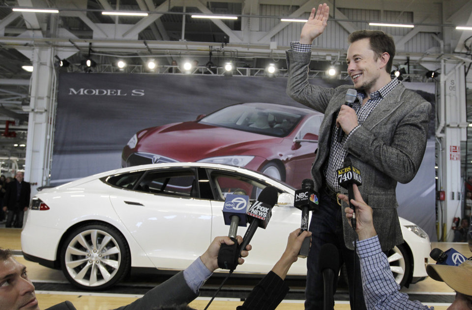 Photo - FILE - In this June 22, 2012 file photo, Tesla CEO Elon Musk waves during a rally at the Tesla factory in Fremont, Calif. Musk has five states bidding up subsidy packages to land a coveted plant for a $5 billion factory to make batteries for a new generation of Tesla electric cars. (AP Photo/Paul Sakuma, File)