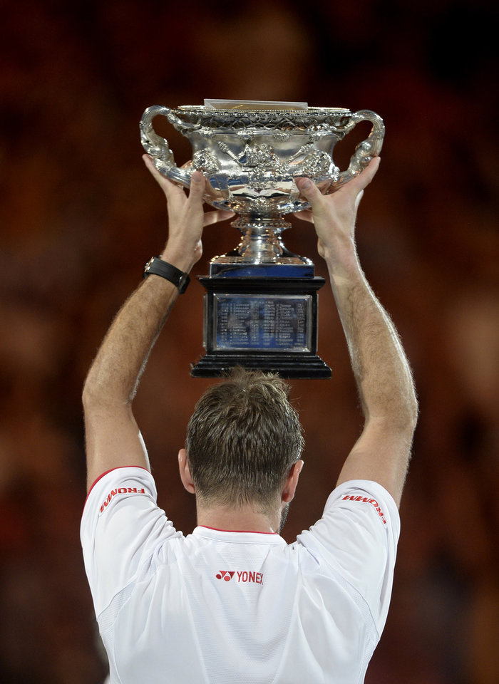 Photo - Stanislas Wawrinka of Switzerland holds up the trophy after defeating Rafael Nadal of Spain in the men's singles final at the Australian Open tennis championship in Melbourne, Australia, Sunday, Jan. 26, 2014. (AP Photo/Andrew Brownbill)
