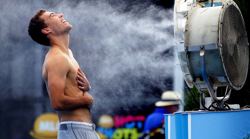 Photo - In this photo released by Tennis Australia, Poland's Jerry Janowicz is sprayed with cool water at the Australian Open tennis championship in Melbourne, Australia, Thursday, Jan. 16, 2014. The Australian Open organizers implemented the Extreme Heat Policy when the temperature topped 43 C (109 F) and play was halted for just over fours on the outside courts but continued on the covered show courts. (AP Photo/Tennis Australia,Fiona Hamilton)