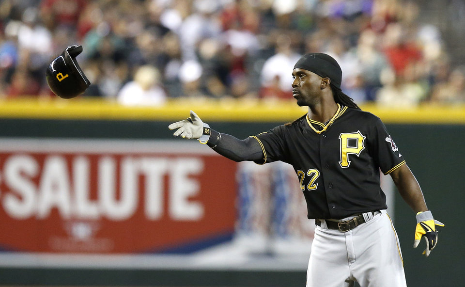 Photo - Pittsburgh Pirates' Andrew McCutchen tosses his helmet to a coach as he is stranded on the bases during the third inning of a baseball game against the Arizona Diamondbacks on Sunday, Aug. 3, 2014, in Phoenix. (AP Photo/Ross D. Franklin)