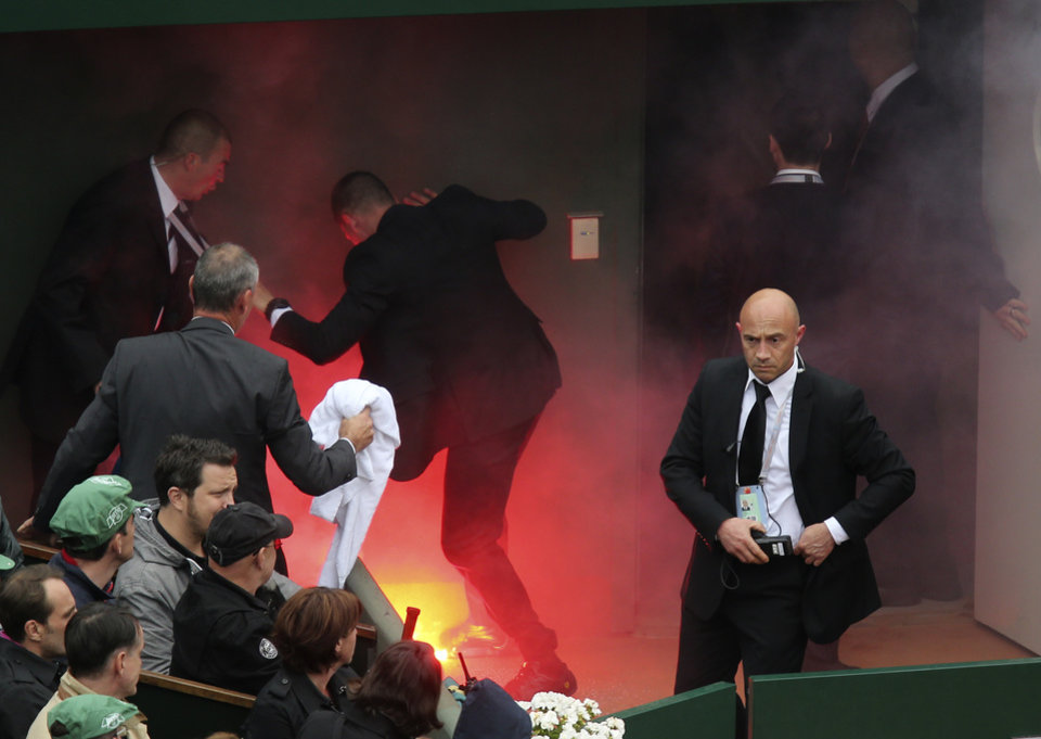 Photo - Security officer try to put out a fire after a demonstrator ran onto center court with flares as Spain's Rafael Nadal plays compatriot David Ferrer during the men's final match of the French Open tennis tournament at the Roland Garros stadium Sunday, June 9, 2013 in Paris. (AP Photo/David Vincent)