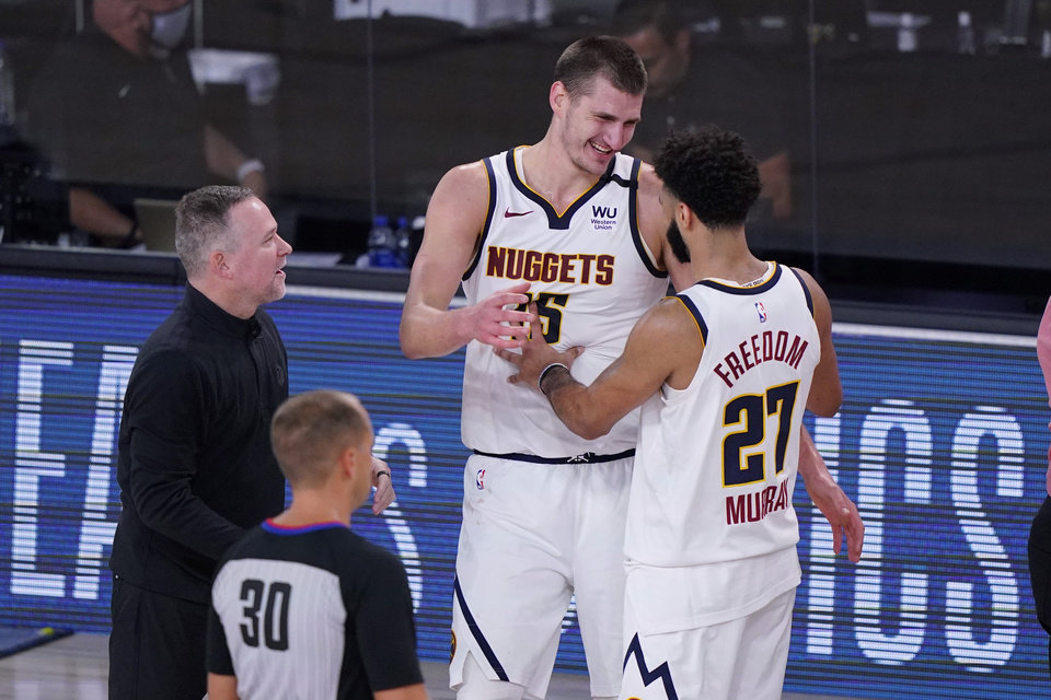 Photo - Denver Nuggets head coach Michael Malone, left, celebrates the team's win over the Los Angeles Clippers with center Nikola Jokic (15) and guard Jamal Murray (27) in an NBA conference semifinal playoff basketball game Tuesday, Sept. 15, 2020, in Lake Buena Vista, Fla. (AP Photo/Mark J. Terrill)