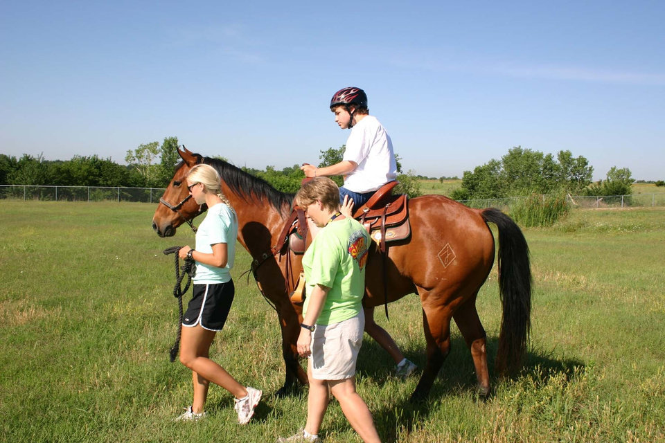 "Camper Mark McBride enjoys his ride on American Quarter Horse King Glo Jessie as one of the many activities of the Movin' & Groovin' summer day camp at the J. D. McCarty Center for children with developmental disabilities in Norman. Leading ""Jessie"" around the pasture is summer day camp volunteer Ashley Birchfield. Acting as one of the side walkers is Jennifer Woodruff, physical therapist and camp director.<br/><b>Community Photo By:</b> Greg Gaston<br/><b>Submitted By:</b> Greg,"