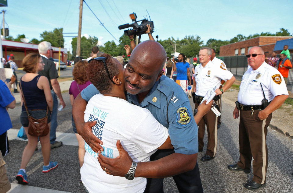 Photo - Capt. Ronald Johnson of the Missouri Highway Patrol hugs Angela Whitman, of Berkeley, Mo., on West Florissant Avenue in Ferguson, Mo., on Thursday, Aug. 14, 2014. The Missouri Highway Patrol seized control of the St. Louis suburb Thursday, stripping local police of their law-enforcement authority after four days of clashes between officers in riot gear and furious crowds protesting the death of an unarmed black teen shot by an officer. (AP Photo/St. Louis Post-Dispatch, David Carson)