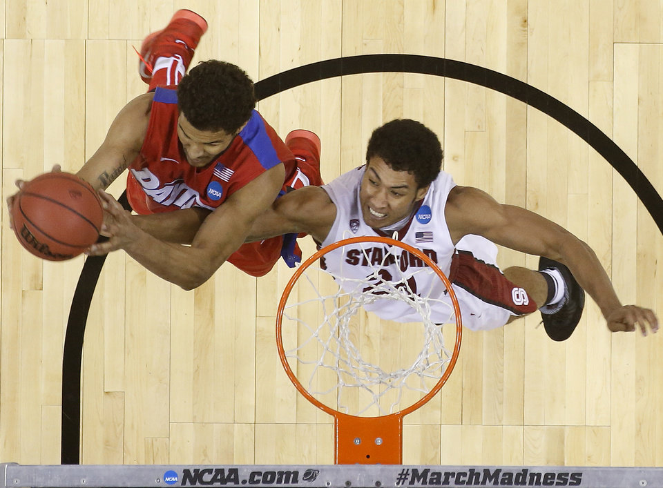 Photo - Dayton forward Devin Oliver (5) shoots on Stanford forward Josh Huestis (24) during the second half in a regional semifinal game at the NCAA college basketball tournament, Thursday, March 27, 2014, in Memphis, Tenn. Dayton won 82-72. (AP Photo/John Bazemore)