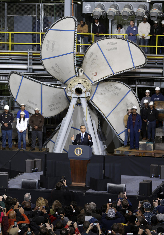 Standing in front of a ships propeller, President Barack Obama gestures as he speaks about about automatic defense budget cuts, Tuesday, Feb. 26, 2013, at Newport News Shipbuilding in Newport News, Va.  (AP Photo/Steve Helber)