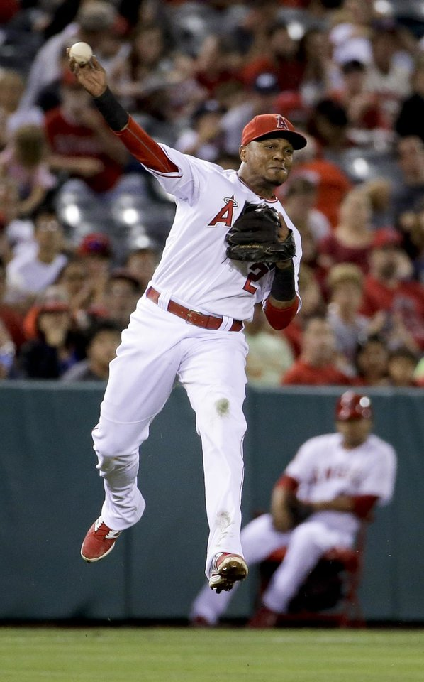 Photo - Los Angeles Angels shortstop Erick Aybar tries to throw out Miami Marlins' Adeiny Hechavarria at second on a single by Donovan Solano during the fifth inning of a baseball game in Anaheim, Calif., Monday, Aug. 25, 2014. Both Marlins were safe on the play. (AP Photo/Chris Carlson)