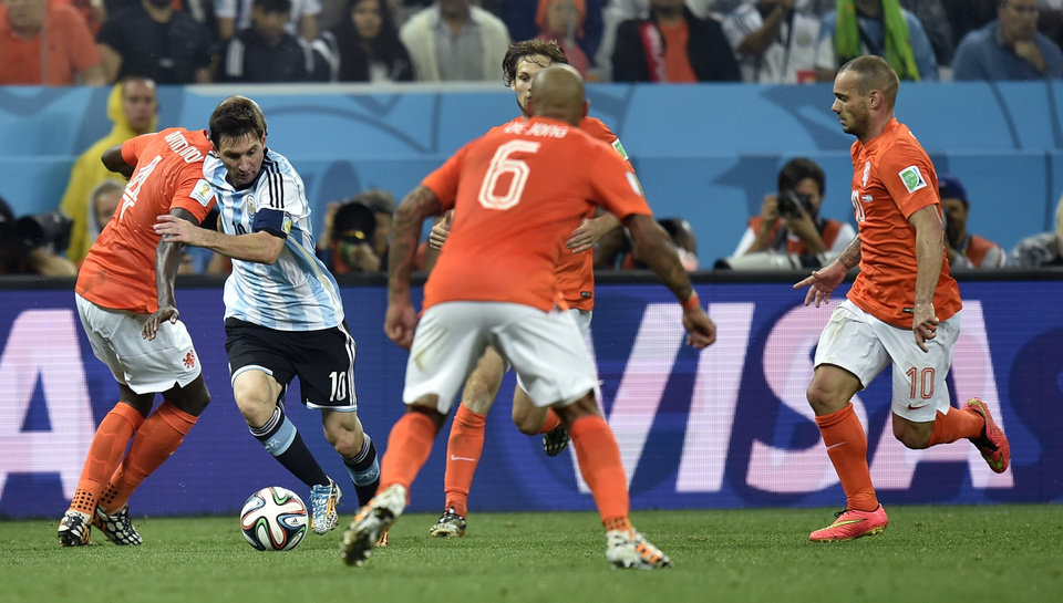 Photo - Argentina's Lionel Messi, second left, takes on the Dutch defence during the World Cup semifinal soccer match between the Netherlands and Argentina at the Itaquerao Stadium in Sao Paulo Brazil, Wednesday, July 9, 2014. (AP Photo/Martin Meissner)