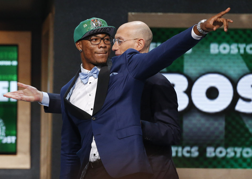 Photo - Oklahoma State's Marcus Smart, left, points to fans after being selected sixth overall by the Boston Celtics during the 2014 NBA draft, Thursday, June 26, 2014, in New York. (AP Photo/Jason DeCrow)