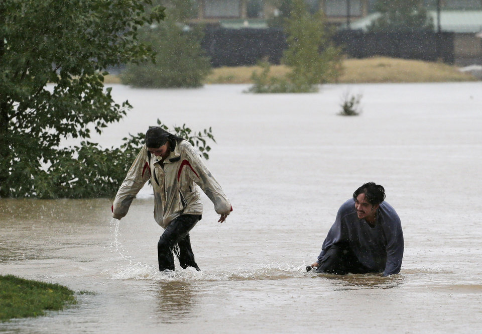 Photo - A couple plays in flood water at Utah Park in Aurora, Colo., on Thursday, Sept. 12, 2013. The park was under water due to flooding. Flash flooding in Colorado has cut off access to towns, closed the University of Colorado in Boulder and left at least three people dead.(AP Photo/Ed Andrieski)