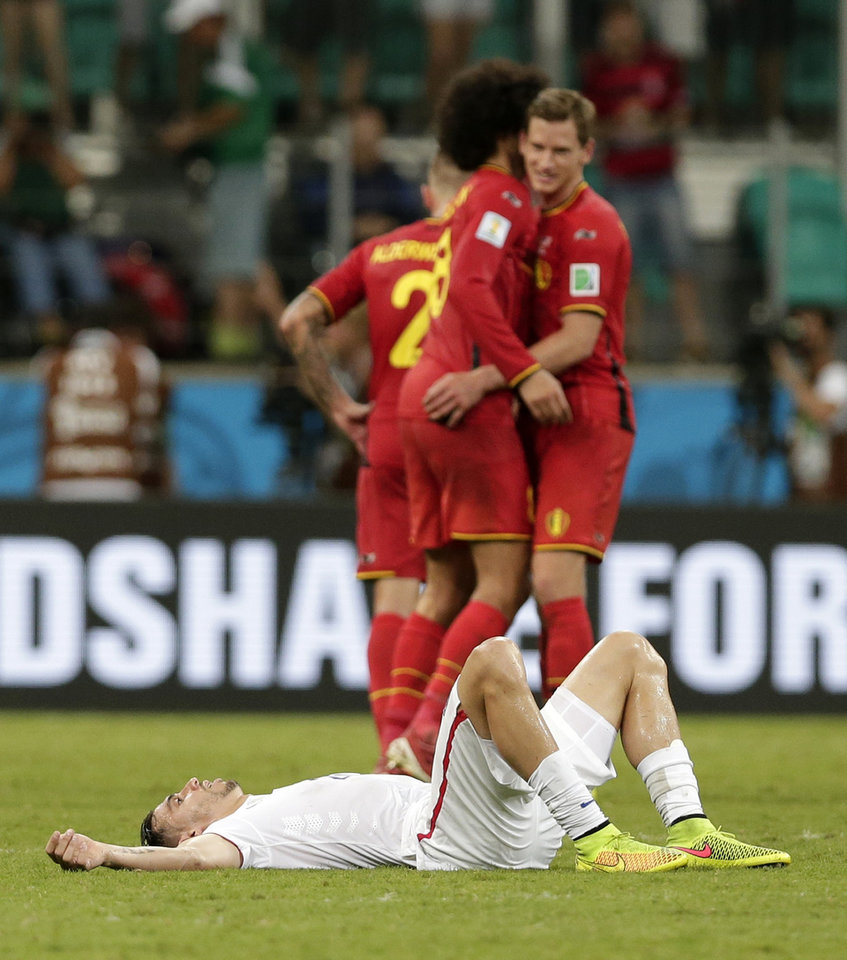 Photo - United States' Geoff Cameron lies on the pitch after Belgium defeated the USA 2-1 in extra time to advance to the quarterfinals during the World Cup round of 16 soccer match between Belgium and the USA at the Arena Fonte Nova in Salvador, Brazil, Tuesday, July 1, 2014. (AP Photo/Marcio Jose Sanchez)
