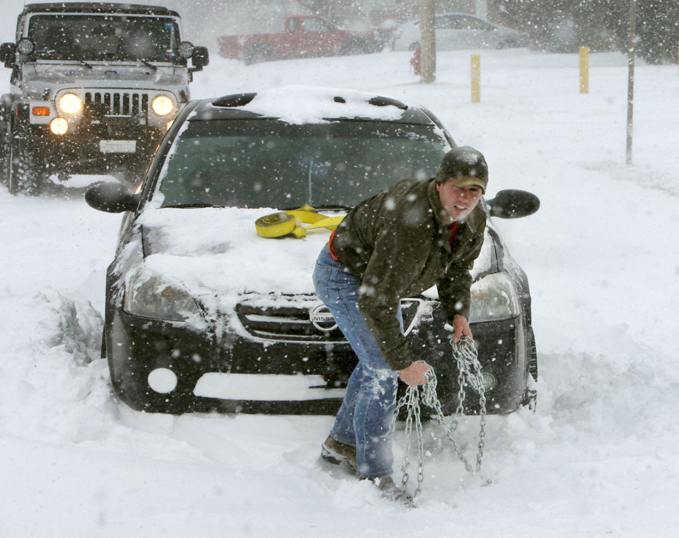 Photo - With bare hands, Josh Fulgium assists a motorist whose car was stuck in drifting snow in Edmond, OK, Tuesday, Feb. 1, 2011. By Paul Hellstern, The Oklahoman